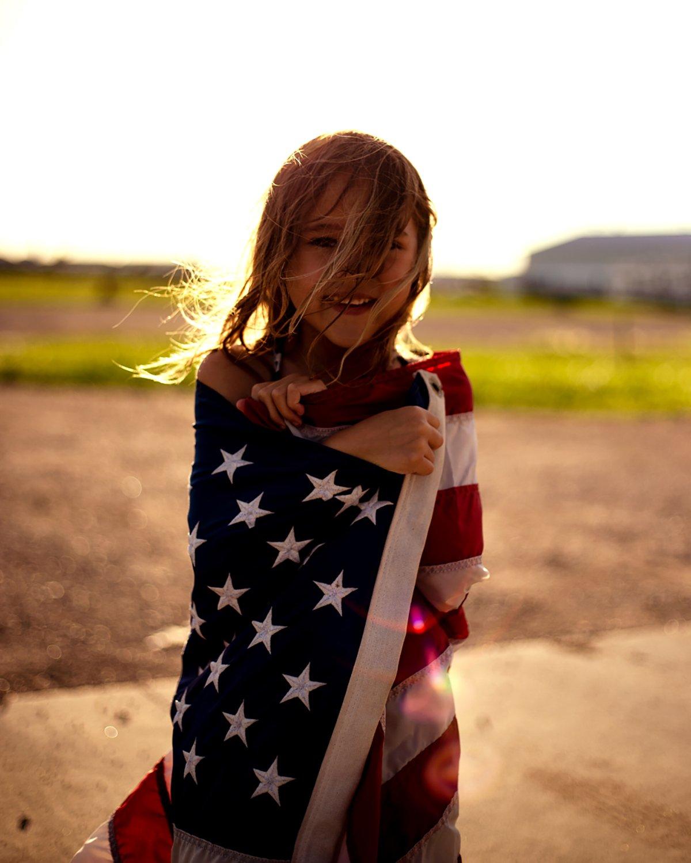 Child portrait draped in flag